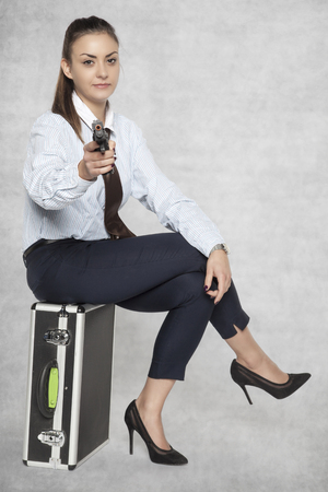 business woman sitting on a suitcase and shoots a gun