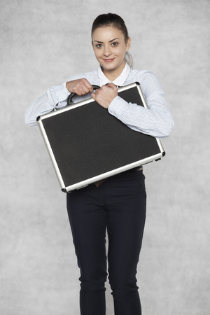 Businesswoman is holding a suitcase with confidential data Banco de Imagens - 93410100