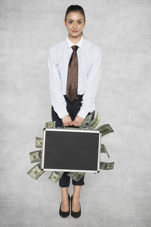 businesswoman is facing front, suitcase stuffed with money Stock Photo