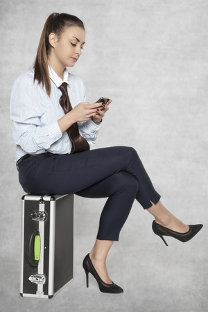 woman sits on a suitcase and sends a text message