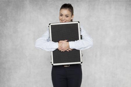 businesswoman squeezes a suitcase with a company documentation Banco de Imagens