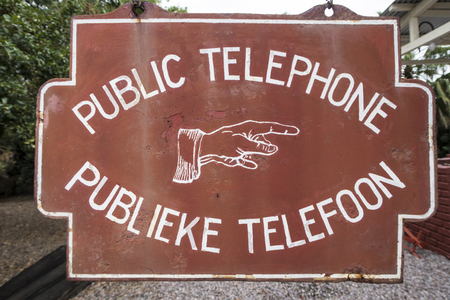 very old information sign about a public telephone, Africa