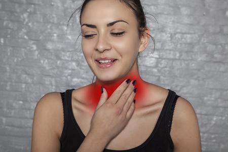 keel besmet met bacteriën, een vrouw die haar keel vasthoudt Stockfoto