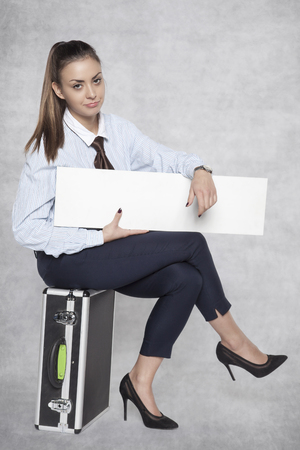 Unhappy business woman sitting on a suitcase and holding an ad on her knees