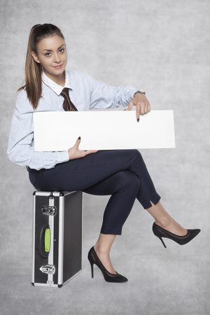 pleasant business woman sits on a suitcase and holds a commercial on her knees