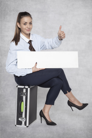 satisfied business woman sitting on a suitcase and holding an advertisement on her lap Stock Photo