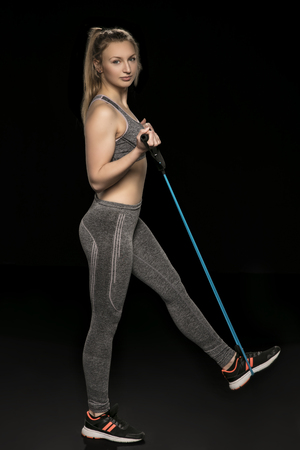 athletic woman stretches elastic rubber, isolated on the black background Stock Photo