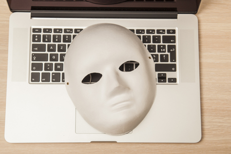Conceptual photo, mask on a laptop as a symbol of a hacker attack, top view