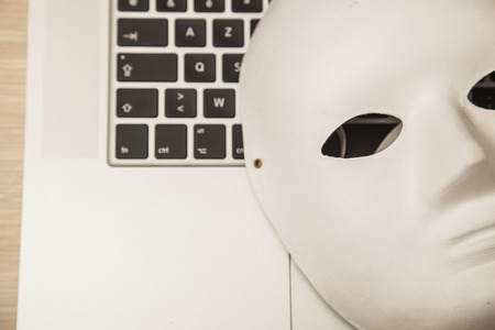 Conceptual photo, mask on a laptop as a symbol of a hacker attack, close up