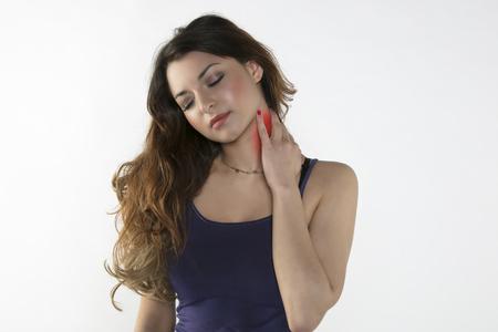 Une jeune femme est aux prises avec la douleur, isolée sur fond Banque d'images