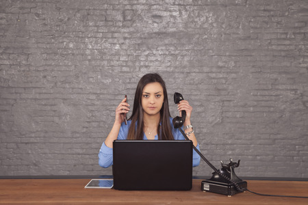 young beautiful secretary to conduct two phone calls at one time, the concept of task-oriented