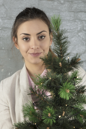 business woman poses for a photo with a Christmas tree, portrait