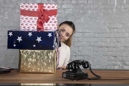 business woman hides behind a pile of presents, view from side Stock Photo