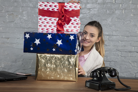 business woman hides behind a pile of presents, close up