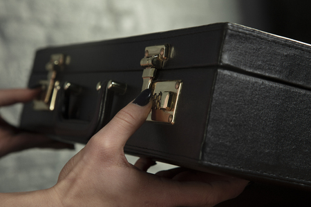 secretary tries to open the encrypted lock in the briefcase