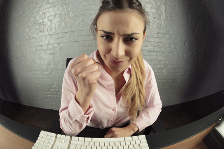 business woman is working on the computer, threatens to punch