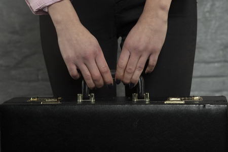 secretary holds a briefcase in her hands