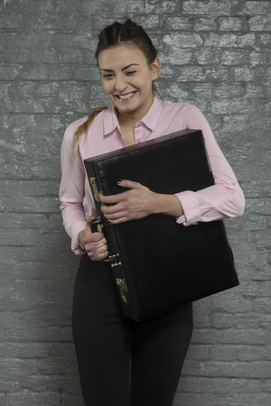 satisfied secretary holds a briefcase, a funny face