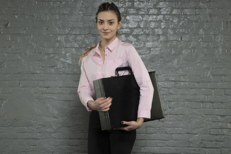 beautiful business woman holding a briefcase under her arm, smile on her face