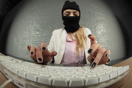 an incognito person steals information from a computer Stock Photo