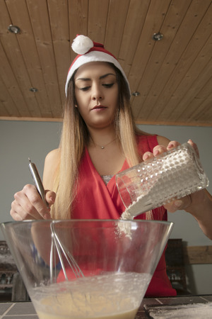 girl in Christmas clothing, adds flour to the cake, close up Reklamní fotografie