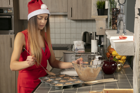 woman in the kitchen is preparing cupcakes for an evening Christmas party