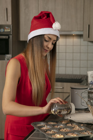 beautiful young girl is preparing Christmas muffins Reklamní fotografie