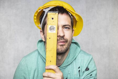the builder holds in his hands the spirit levels, the idea of accuracy in the construction Stok Fotoğraf