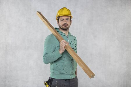 the construction worker holds a piece of board in his hands, the concept of choosing wood for construction