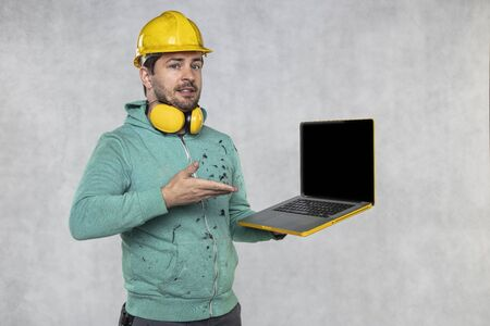 modern building supervisor keeps the computer in his hands, technology at work Stockfoto