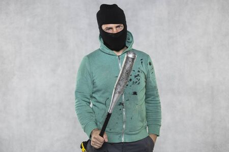 a masked hooligan holds a baseball bat in his hand