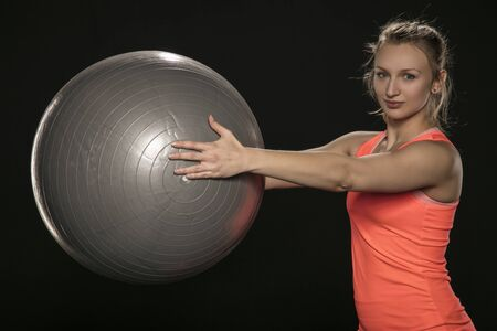 young athletic girl exercising with a large rubber ball
