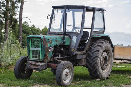 old green tractor standing outside