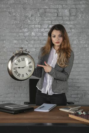 business woman holds watch and shows hour, portrait