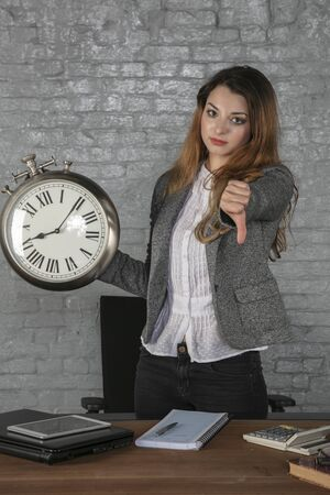 business woman holds watch and shows thumb down