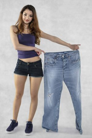 young beautiful athletic girl shows how much weight she lost