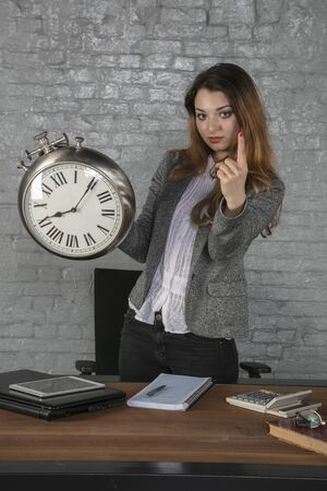business woman holds watch and gives finger warning