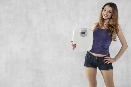 young beautiful girl with a weight, weight loss symbol