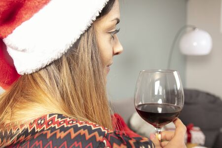 young lonely girl drinks wine at Christmas