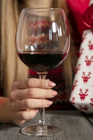young beautiful girl wraps presents for Christmas, drinking wine