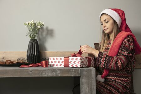 Young beautiful girl busy wrapping a gift for Christmas