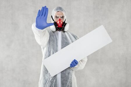 virologist in protective clothing holds advertising space in his hands Standard-Bild