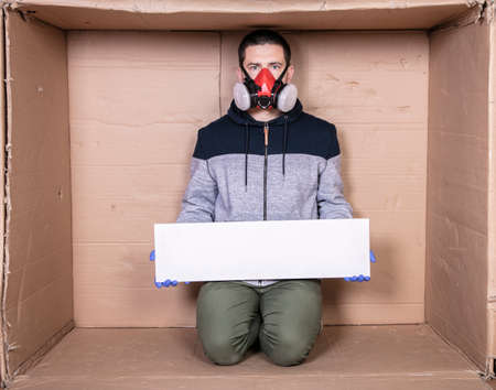 man in a protective mask is sitting in a cardboard box, holding an empty board with a place for an advertisement