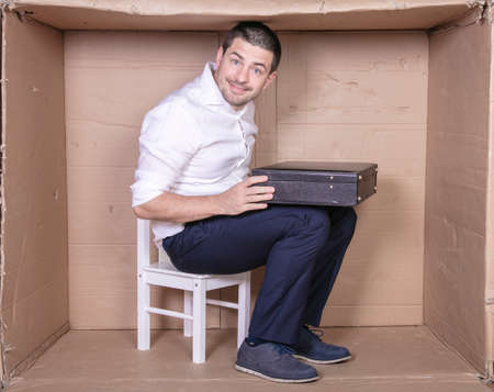 businessman with a briefcase sits in a tight cardboard box imitating an office