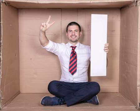 businessman shows a victory symbol, holds copy space in other hand