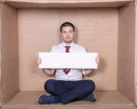 businessman holding copy space in front of him, seated in a small tight office