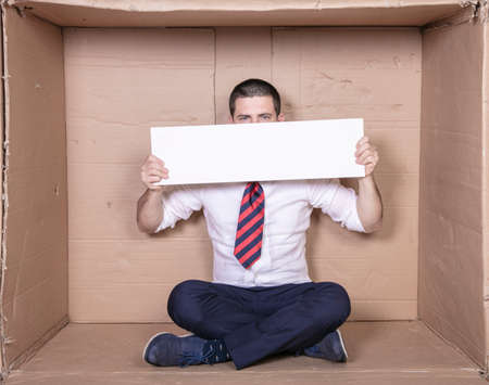 businessman covers his face with advertising space, cramped rented office