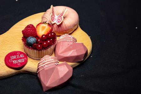 set of tasty sweets lies on a wooden board, black background Reklamní fotografie