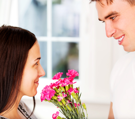 Men giving flowers to his lover woman.