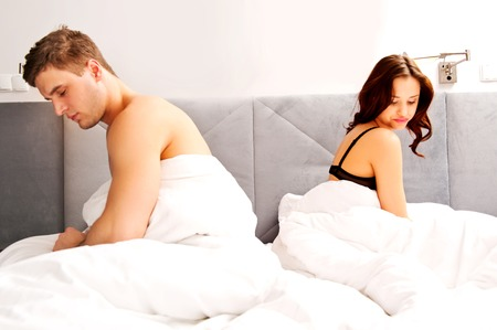 Young couple in bed after argue.